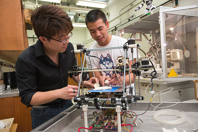 Senior chemical engineering student Derek Chhiv, right, discusses with Professor Anson Ma his group's prototype for an artificial kidney. The prototype was generated through 3-D printing.