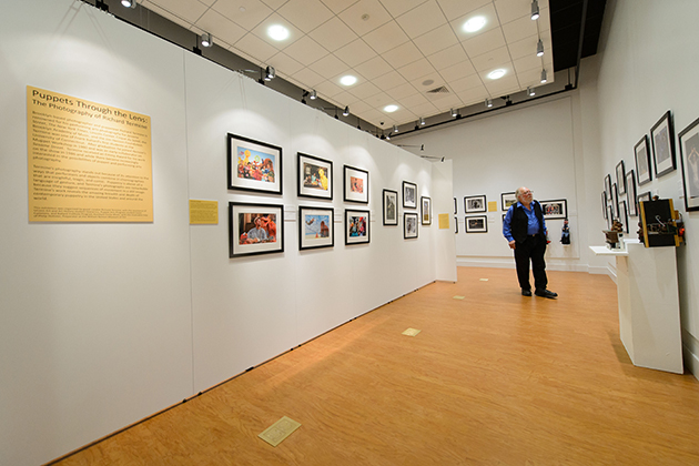 Bart Roccoberton, professor of dramatic arts, looks over an exhibit of photography by Richard Termine '75 (SFA), 'Puppets Through the Lens.' The Ballard Institute and Museum of Puppetry's new home includes expanded exhibition and performance space. (Peter Morenus/UConn Photo)