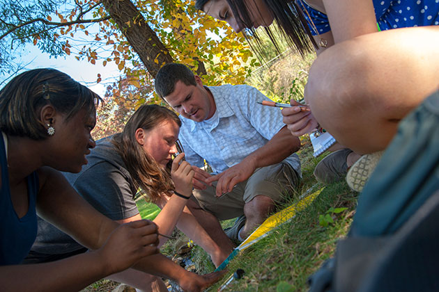 From left, Tiffany Cousins '14, Kamilla Dynia '14, Kevin Evringham, graduate teaching assistant for Professor John Jolly-Ballantine, and Victoria Chilinski '16, look over water samples during an outdoor geography class near Mirror Lake. (Sean Flynn/UConn Photo)