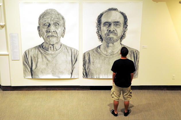 Stephen Quesnel '14 (BUS) views charcoal portraits of Arthur, left, and Ralph (Ray) by Ray Di Capua, two of the faculty artworks on display at the Benton Museum. Di Capua is an associate professor of art and art history. (Max Sinton '15 (CANR)/UConn Photo)