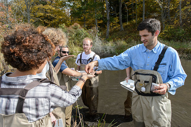 Mark Urban, right, assistant professor of ecology and evolutionary biology, leads a class on the study of freshwater habitats. (Peter Morenus/UConn Photo)
