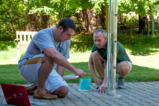 Michael Dietz, assistant Cooperative Extension educator-in-residence, right, and environmental science major Alexander Barresi '14 (CAHNR) record the surface infiltration rate of pervious pavement outside the Lakeside Building on North Eagleville Road.